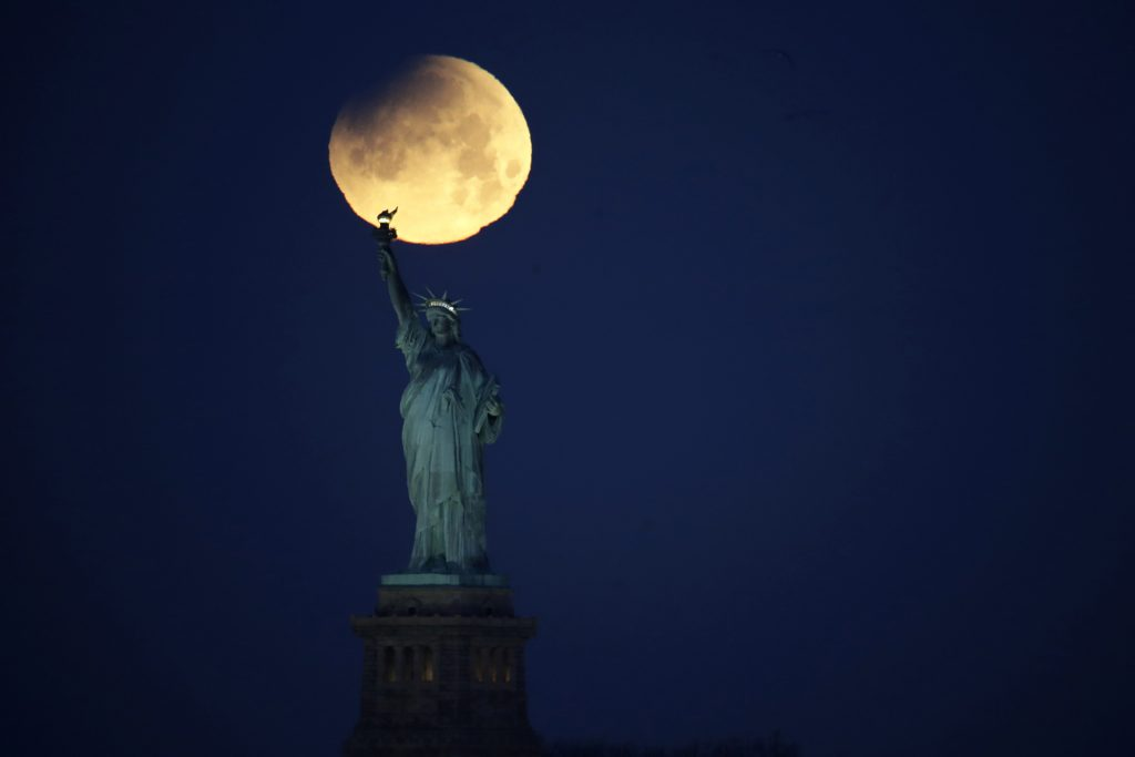 The Statue of Liberty is backdropped by a supermoon, Wednesday, Jan. 31, 2018, seen from the Brooklyn borough of New York. The supermoon, which is the final of three consecutive supermoons, also experience lunar eclipse as it set over the horizon, but only a partial eclipse was visible in the East Coast. (AP Photo/Julio Cortez)