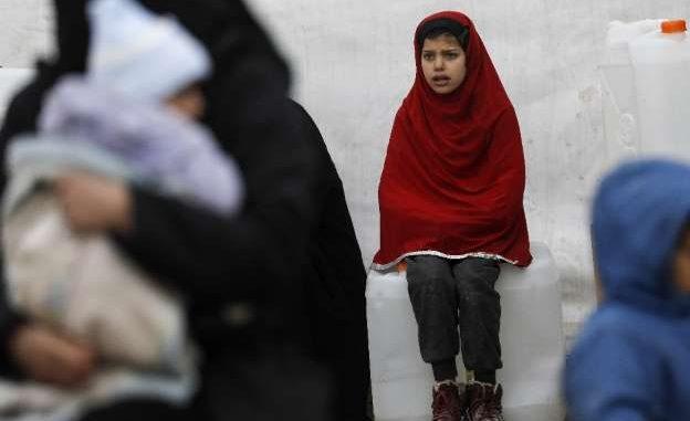 Una niña siria observa como se descargan elementos de ayuda para tolerar el frío